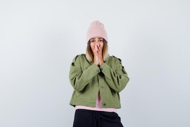 Giovane donna che indossa una giacca scioccata