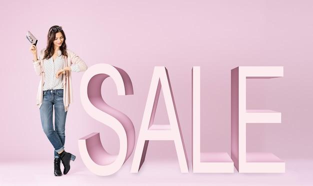 販売サインに傾いてジャケットを着ている若い女性
