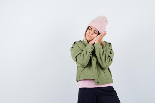 Young woman wearing a jacket pretending to sleep