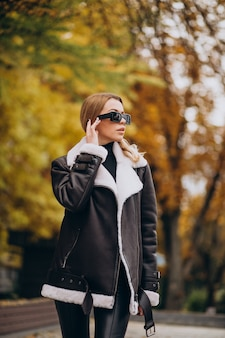Молодая женщина в куртке гуляет на улице