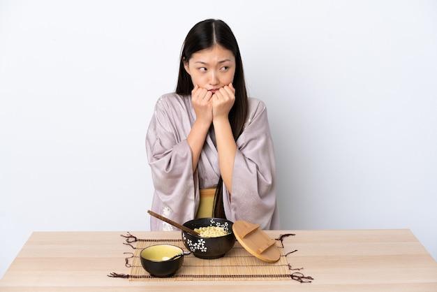 着物を着て、緊張した麺を食べる若い女性