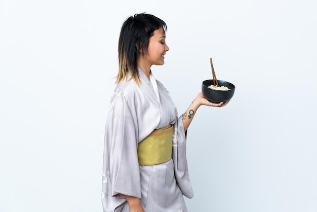 幸せな表情で孤立した白い背景に麺のボウルを保持している着物を着た若い女性