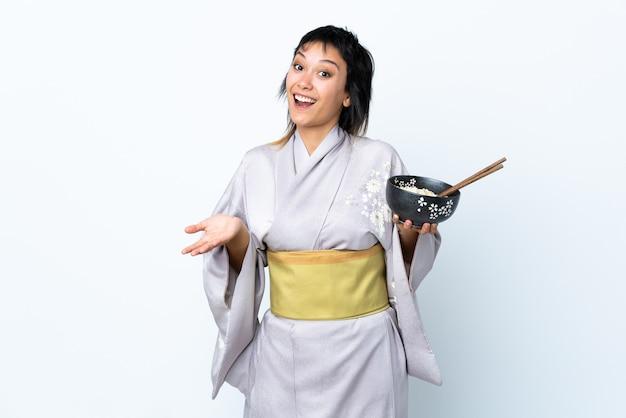 ショックを受けた表情で孤立した白い背景に麺のボウルを保持している着物を着た若い女性