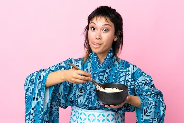 孤立した白い背景の上に麺のボウルを保持している着物を着た若い女性