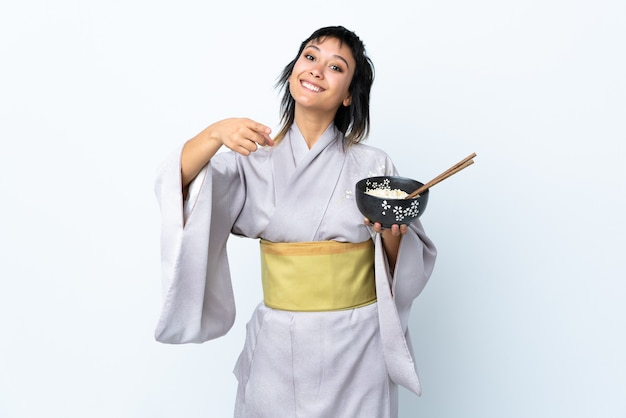 Young woman wearing kimono holding a bowl of noodles on isolated white points finger at you with a confident expression