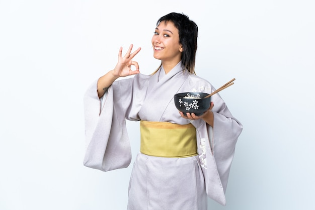 Young woman wearing kimono holding a bowl of noodles over isolated white showing ok sign with fingers