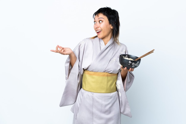 Young woman wearing kimono holding a bowl of noodles over isolated white space with surprise facial expression