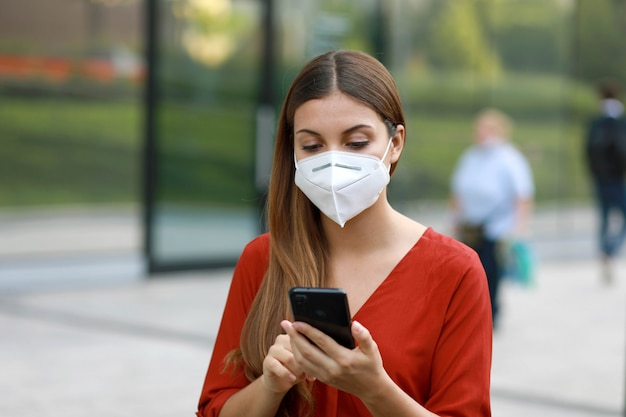 Young woman wearing kn95 ffp2 mask using mobile phone app in city street to aid contact tracing and self diagnostic in response to coronavirus