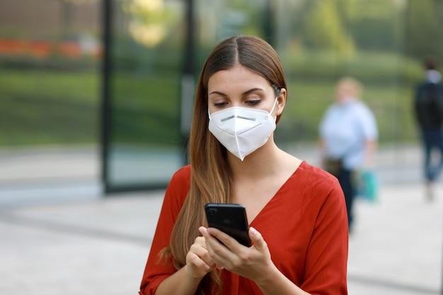 Молодая женщина в маске kn95 ffp2 использует приложение для мобильного телефона на городской улице для помощи в отслеживании контактов и самодиагностики в ответ на коронавирус