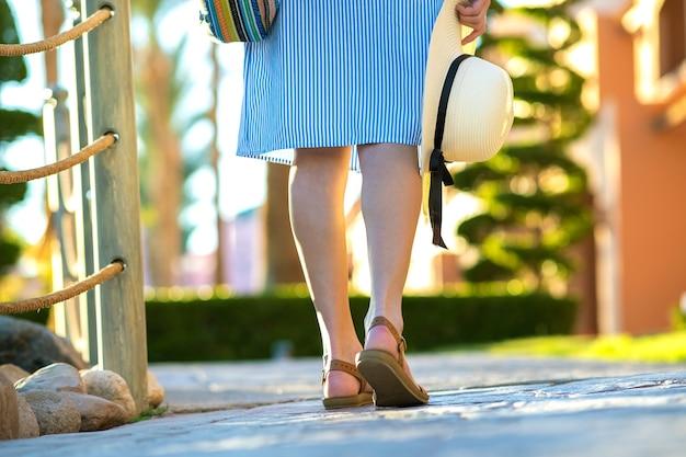 Молодая женщина в голубом летнем платье держит модную сумку через плечо и желтую соломенную шляпу, стоя снаружи, наслаждаясь теплой погодой в летнем парке.