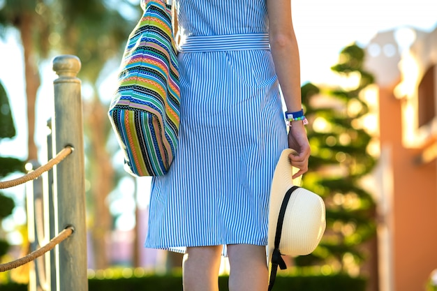 Young woman wearing light blue summer dress holding fashionable shoulder bag and yellow straw hat standing outside enjoying warm weather in summer park