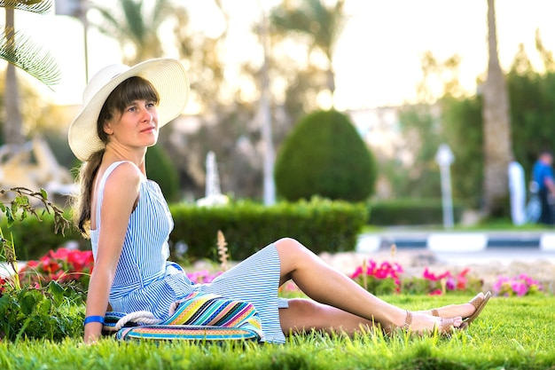 Young woman wearing light blue summer dress and yellow straw hat relaxing on green grass