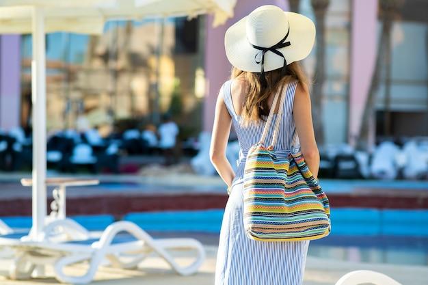 夏の晴れた日にホテルの外に立っているファッショナブルなショルダーバッグを保持している明るい夏のドレスと黄色の麦わら帽子を身に着けている若い女性。
