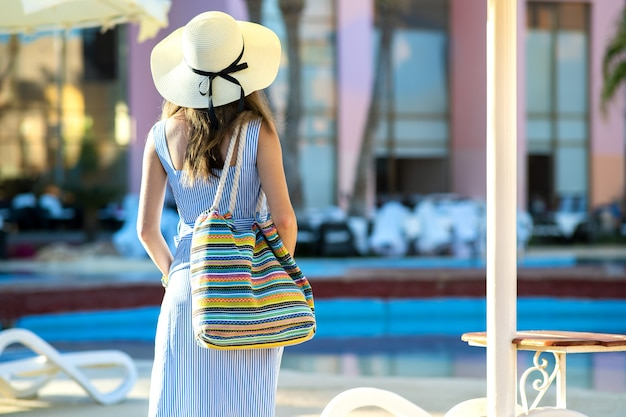 Young woman wearing light summer dress and yellow straw hat holding fashionable shoulder bag standing outside hotel on summer sunny day.