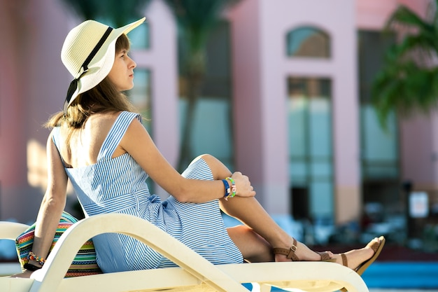 Young woman wearing light summer dress and yellow straw hat sitting outside near hotel swimming pool on summer sunny day