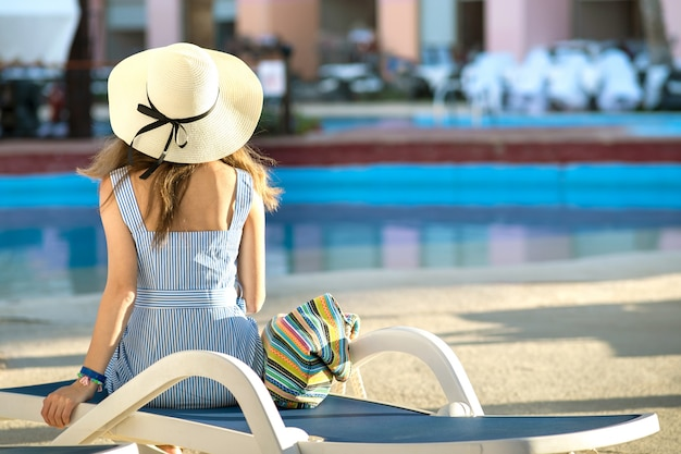 Young woman wearing light summer dress and yellow straw hat sitting outside near hotel swimming pool on summer sunny day.