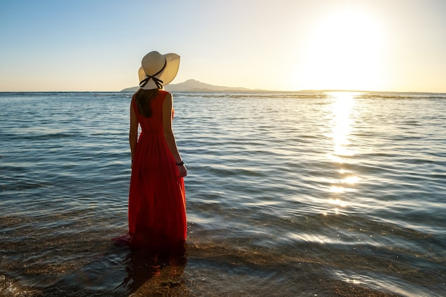 긴 빨간 드레스와 밀짚모자를 쓴 젊은 여성이 이른 여름 아침에 떠오르는 태양을 바라보며 해변의 바닷물에 서 있습니다.