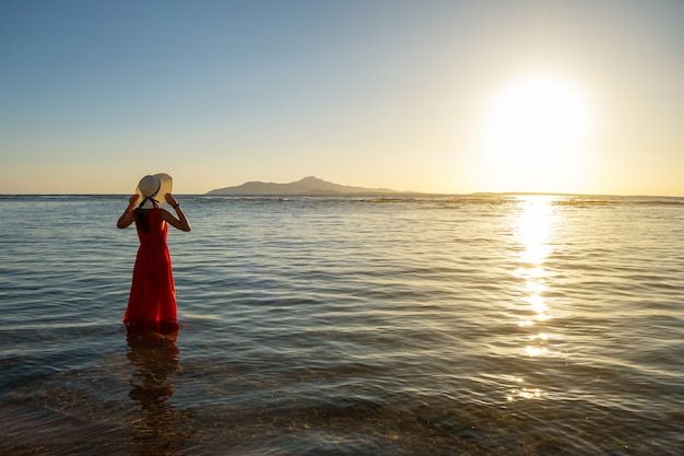 이른 여름 아침에 떠오르는 태양의 전망을 즐기는 해변에서 바닷물에 긴 빨간 드레스와 밀짚 모자 서 입고 젊은 여자.