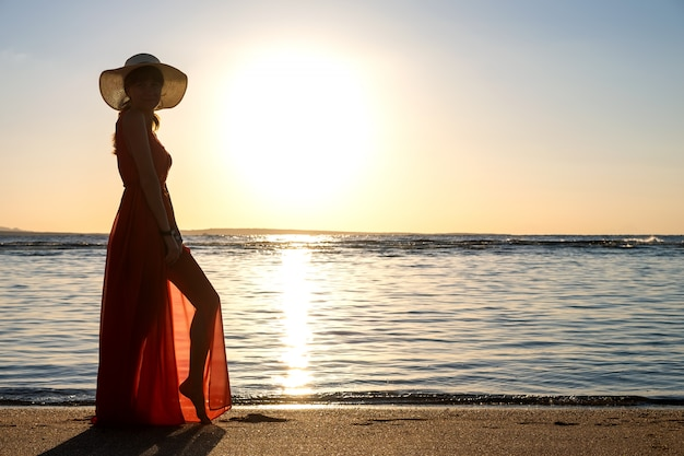 Молодая женщина нося длинное красное платье и соломенную шляпу стоя на береге пляжа песка на море наслаждаясь взглядом восходящего солнца в утре раннего лета.