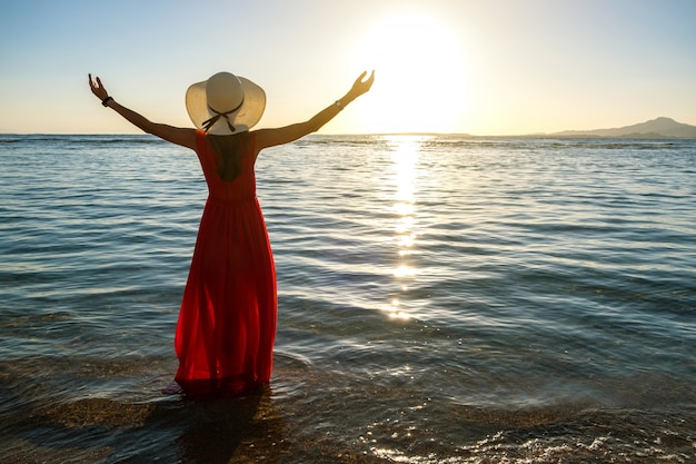 Young woman wearing long red dress and straw hat raising hands standing in sea water at the beach enjoying view of rising sun in early summer morning.