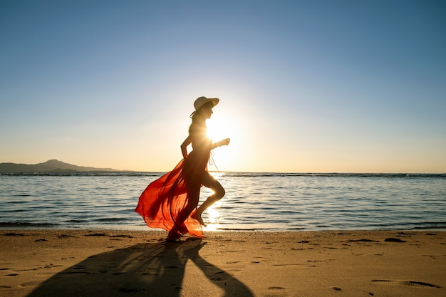 Young woman wearing long red dress and straw hat running on sand beach at sea shore enjoying view of rising sun in early summer morning.