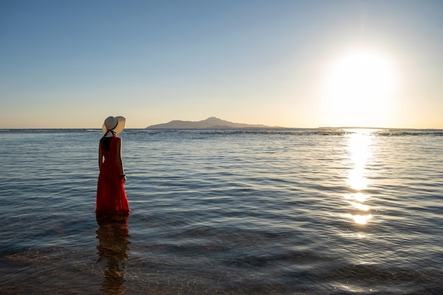 Young woman wearing long red dress and straw hat standing in sea water at the beach enjoying view of rising sun in early summer morning.