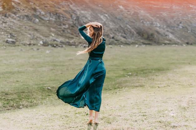 風の中でフィールドに立って、長い絹のドレスを着て若い女性