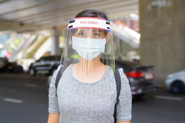 街の通りでコロナウイルスの発生から保護するためのマスクとフェイスシールドを身に着けている若い女性
