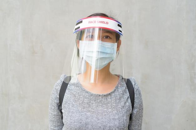 屋外でコロナウイルスの発生から保護するためのマスクとフェイスシールドを身に着けている若い女性