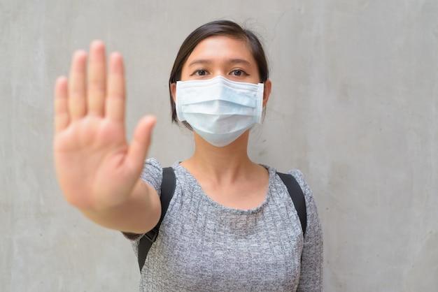 マスクを着用し、屋外で停止ジェスチャーを示す若い女性