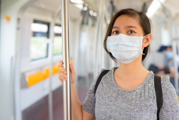 コロナウイルスの発生から保護するためにマスクを着用し、電車の中で距離を置いて立っている若い女性