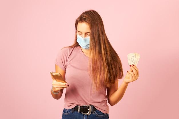 スマートフォンと映画のチケットを保持しているマスクを身に着けている若い女性