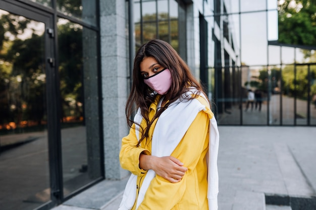 Молодая женщина в маске позирует на улице.