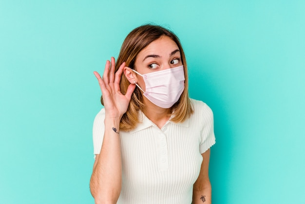 Young woman wearing a mask for virus isolated on blue wall trying to listening a gossip.