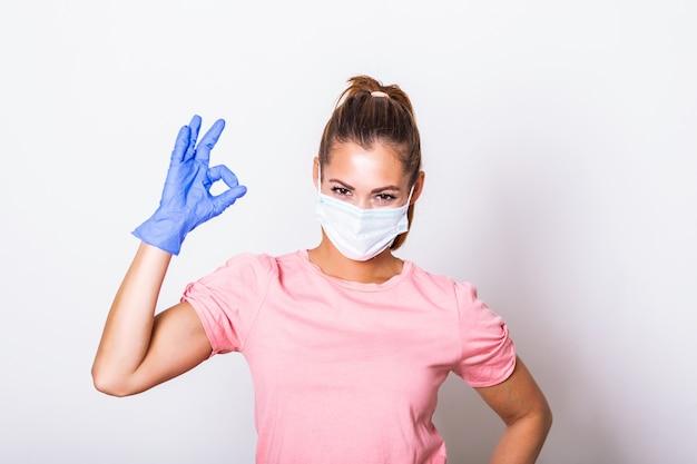 医療用フェイスマスクを身に着けているとokサインを示す若い女性。コロナウイルスのサージカルマスクを着ている女性