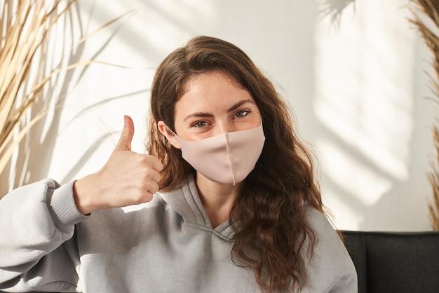 Молодая женщина в медицинской маске. женщина, носящая защитную маску многоразового использования и показывающая большой палец вверх по знаку. женщина в тканевой маске от вируса короны