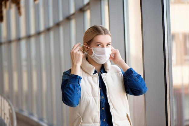 空港ラウンジで医療マスクを身に着けている若い女性