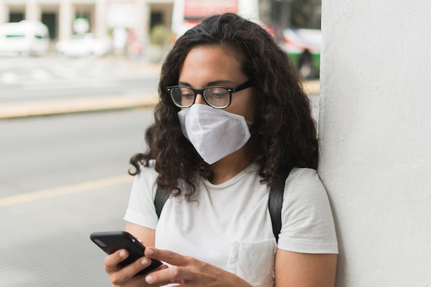Young woman wearing a medical mask while checking her phone