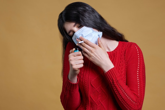 Young woman wearing medical protective mask and holding a cigarette in her mouth through the mask