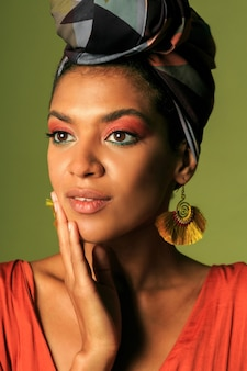 Young woman wearing orange dress with turban and ethnic jewelry