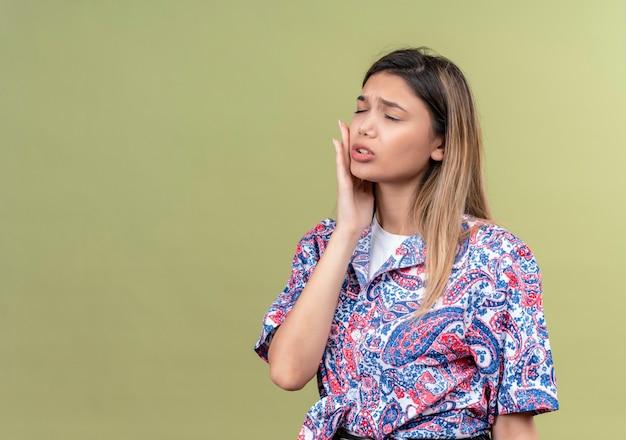 Una giovane donna che indossa una camicia stampata paisley tenendo la mano sulla guancia mentre si sente male e ha mal di denti