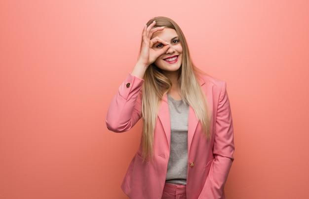 Молодая женщина в пижаме уверенно делает хорошо жест на глаз