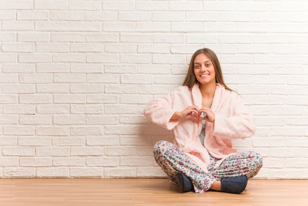 Young woman wearing pajama doing a heart shape with hands