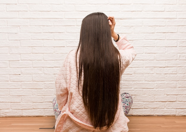 Young woman wearing pajama from behind thinking about something