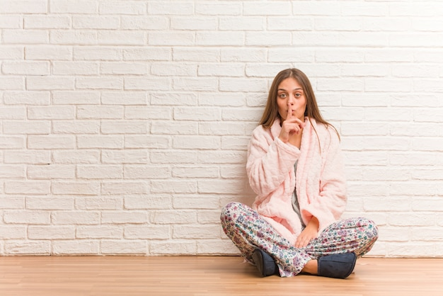 Young woman wearing pajama keeping a secret or asking for silence