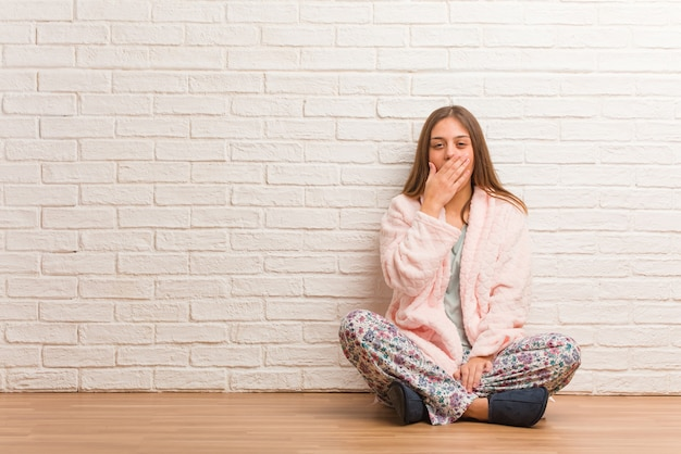 Young woman wearing pajama tired and very sleepy