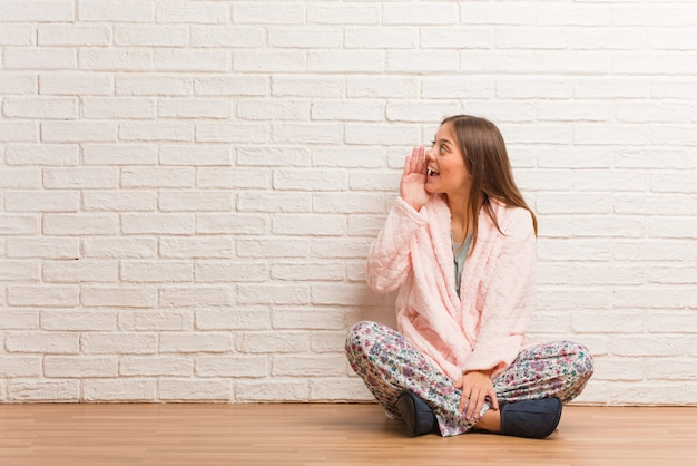 Young woman wearing pajama whispering gossip undertone