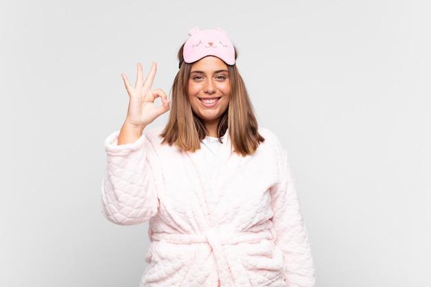 Молодая женщина в пижаме, чувствует себя счастливой, расслабленной и удовлетворенной, демонстрирует одобрение жестом, улыбаясь