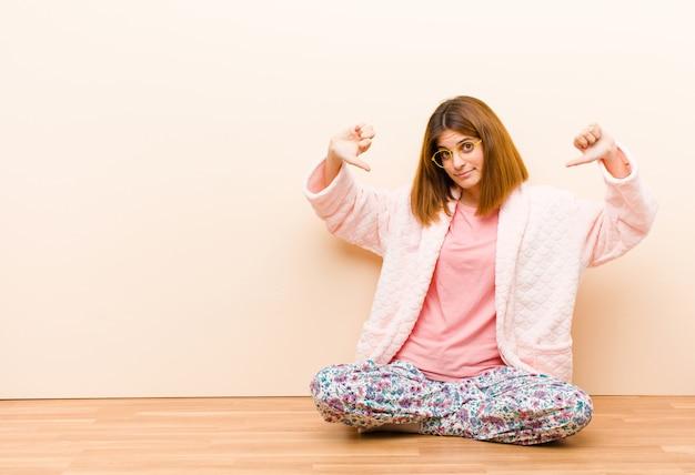 自宅で座っているパジャマを着て悲しい、失望した、または怒っている若い女性、不一致で親指を下に向け、不満を感じている