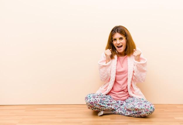 Молодая женщина в пижаме сидит дома и агрессивно кричит с раздраженным, разочарованным, злым взглядом и сжатыми кулаками, чувствуя ярость